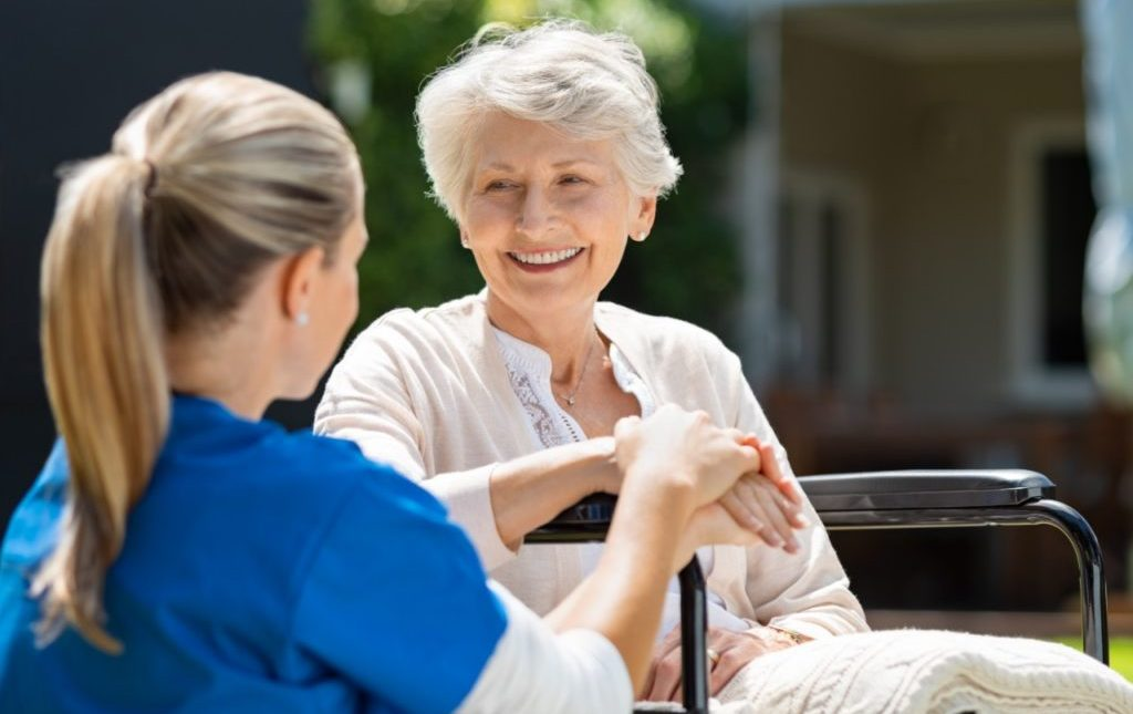 Active Senior sitting with a nurse potentially discussing, Providence House Assisted Living