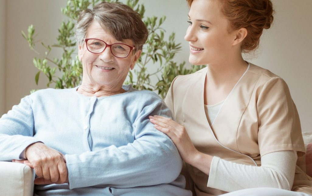 Active Senior sitting with a nurse potentially discussing, and praising Providence House Assisted Living
