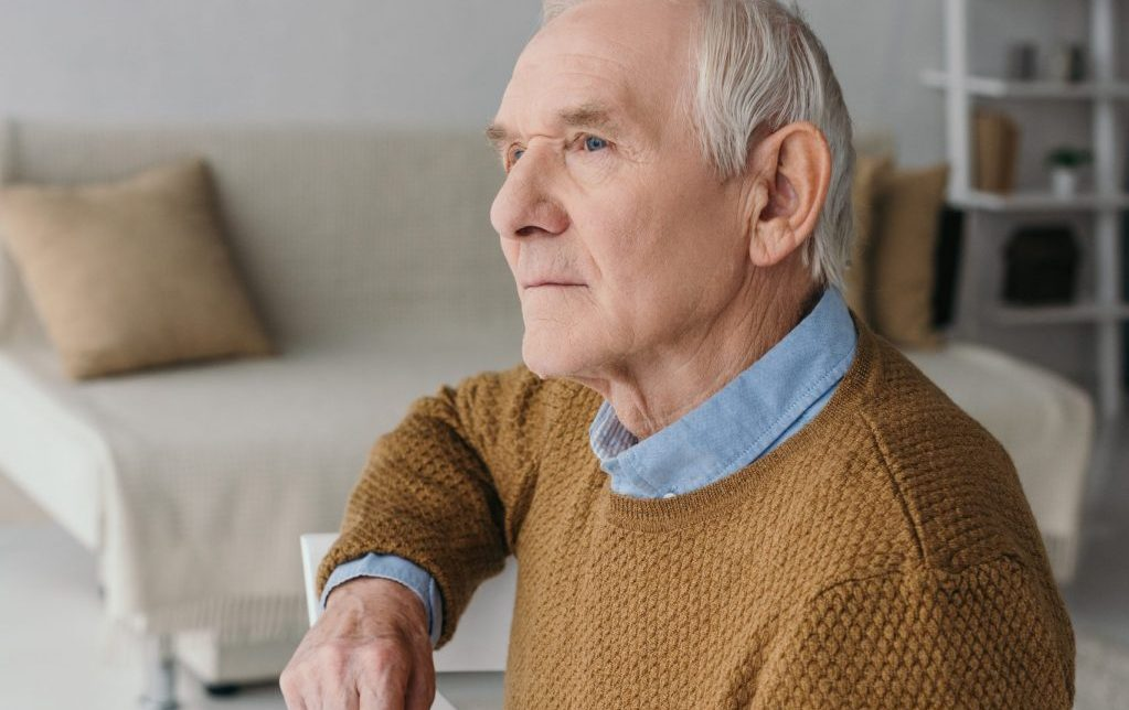 Active Senior sitting potentially thinking of, and experiencing Providence House Assisted Living Facility