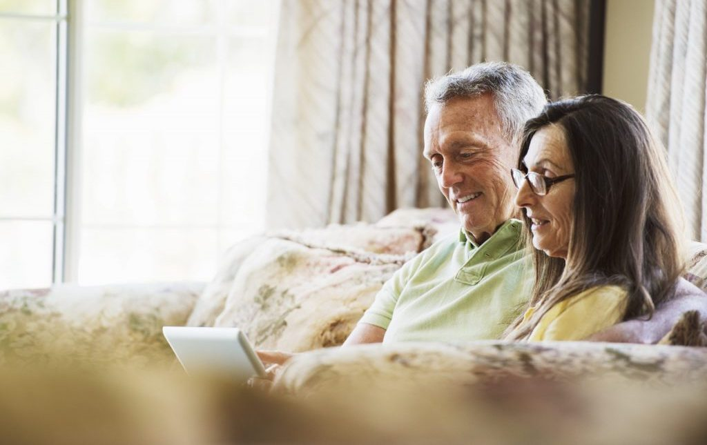 A Senior Couple using an Ipad to potentially look up Assisted Living Blogs such as Providence House Assisted Living